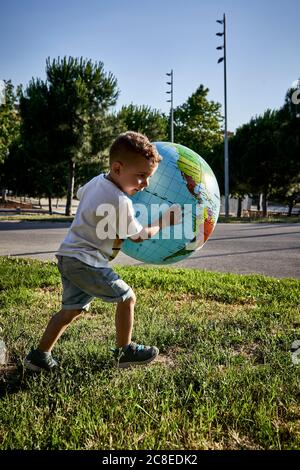 Carefree boy holding globe while running on grassy land during sunny day - Stock Photo