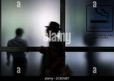 A smoker in a smoking area of a building in Roppongi, Tokyo, Japan Thursday June 27th 2013 - Stock Photo