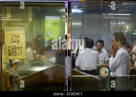 A smoking room in Tokyo Station, Tokyo, Japan. Friday August 21st 2015 - Stock Photo
