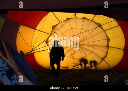 Silhouette of a pilot and crews checking inside the balloon before taking off at Singha Park in Chiang Rai, Thailand.