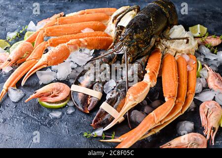 Delicious fresh fish and seafood on dark vintage background. Fish, clams and shrimps with aromatic herbs, spices and vegetables - healthy food, diet o