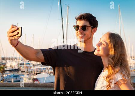 young couple tahe selfie in the sunset light - two young tourist take selfie in a tourist port - Stock Photo