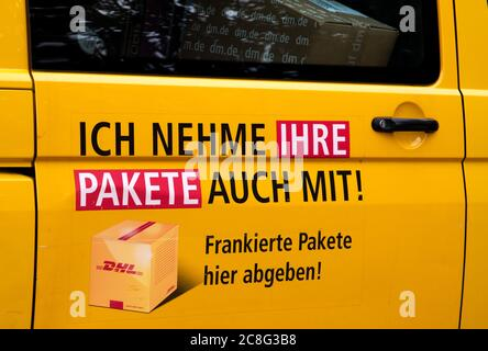 Door of a DHL transporter with the indication that parcels are being taken along. (Ich nehme auch ihre Pakete mit)
