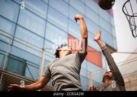 two young asian men playing basketball going up for a rebound on outdoor court - Stock Photo