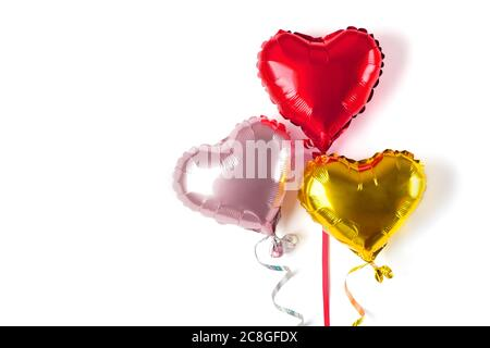 set of three inflatable heart in golden, red, matte pink color isolated on white background Flat lay Top view Holiday card Happy Valentine's day - Stock Photo
