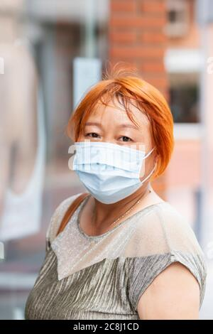 Close up of a mature asian woman wearing a surgical mask looking at the camera on an out of focus background. Safety concept. - Stock Photo