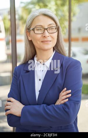 Portrait of confidence and success. Beautiful mature business woman wearing eyeglasses, looking aside and thinking about something while standing outdoors. Vertical shot. Business people