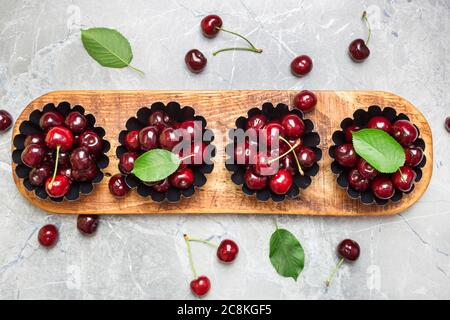 Flat lay composition with sweet cherries on marble table, space for text.