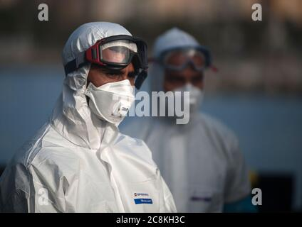Members of European Border and Coast Guard Agency (Frontex) dressed in a protective suits on a patrol vessel at Malaga port after intercepted a dinghy on the Mediterranean Sea.A Spanish Civil Guard vessel intercepted around 82 Algerian migrants near Almeria's coast while trying to reach Europe by small boats. During the coronavirus pandemic, the closure of Morocco's border with Spain as a measure to prevent the spread of coronavirus disease has caused a drastic drop in the number of migrants that try to reach the Spanish coasts across Alboran Sea route, while the arrival of migrants to Canary - Stock Photo