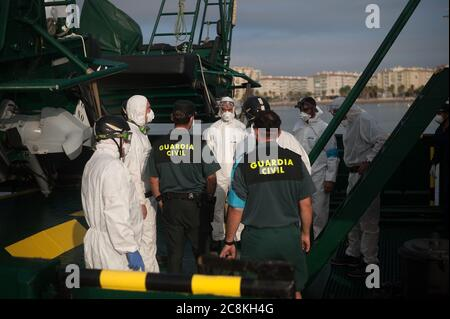 Members of European Border and Coast Guard Agency (Frontex) and Spanish Civil Guard on a patrol vessel at Malaga port after intercepted a dinghy on the Mediterranean Sea.A Spanish Civil Guard vessel intercepted around 82 Algerian migrants near Almeria's coast while trying to reach Europe by small boats. During the coronavirus pandemic, the closure of Morocco's border with Spain as a measure to prevent the spread of coronavirus disease has caused a drastic drop in the number of migrants that try to reach the Spanish coasts across Alboran Sea route, while the arrival of migrants to Canary Island - Stock Photo