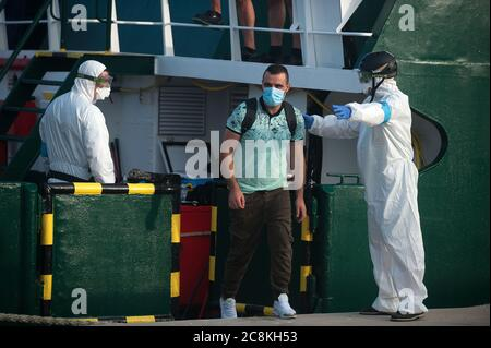 Members of European Border and Coast Guard Agency (Frontex) help a migrant to disembark from a patrol vessel at Malaga port after being intercepted by Spanish Civil Guards authorities on the Mediterranean Sea.A Spanish Civil Guard vessel intercepted around 82 Algerian migrants near Almeria's coast while trying to reach Europe by small boats. During the coronavirus pandemic, the closure of Morocco's border with Spain as a measure to prevent the spread of coronavirus disease has caused a drastic drop in the number of migrants that try to reach the Spanish coasts across Alboran Sea route, while t - Stock Photo