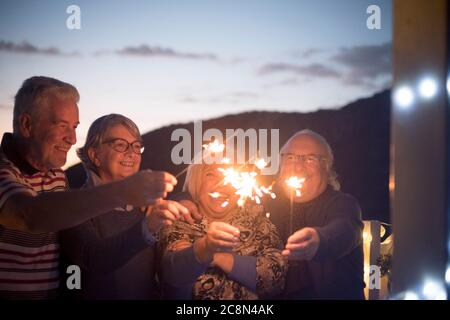 Aged senior people friends have fun and celebrate by night with fire sparkler - concept of new year eve and mature retired couples enjoy friendship at - Stock Photo