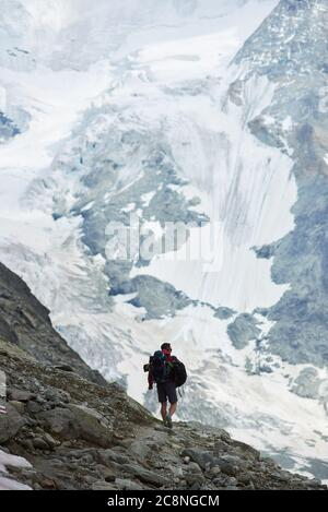 Back view of alone tourist with backpack walking on rocks, beautiful mountains scenery on background. Trekking, man reaching peak. Wild nature with amazing views. Sport tourism in Alps.