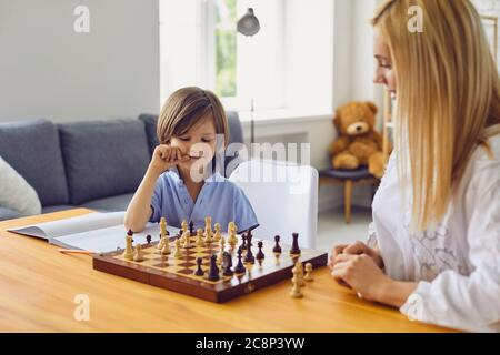 Family hobbies. Young mother playing chess with son at home. Little boy engaged in board game with his parent in room