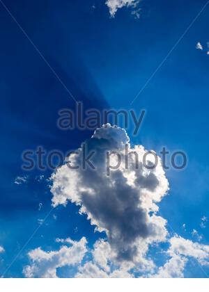 Dark Blue sun rays sunrays near behind White clouds cloud view against sky sunshine sunlight sunny - Stock Photo
