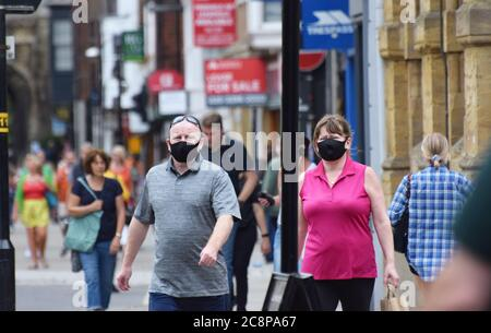 An overweight man and woman wearing face masks in public in England following a law being passed making wearing face coverings compulsory in shops - Stock Photo