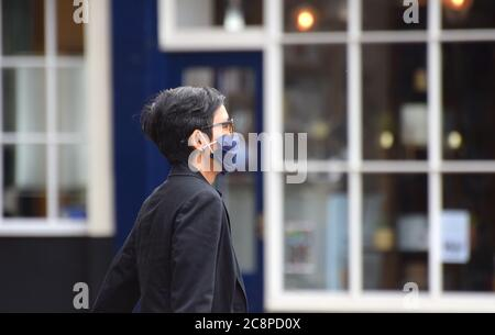 A woman walks along the street in England following a law being passed making wearing face coverings compulsory in Retail Settings on July 24 2020 - Stock Photo