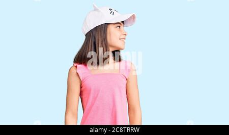 Young little girl with bang wearing funny kitty cap looking away to side with smile on face, natural expression. laughing confident. - Stock Photo