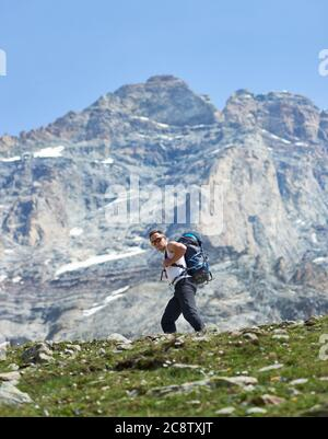 Male mountaineer in sunglasses hiking alone in mountainous region. Hiker with backpack walking along rocky trail with Matterhorn mountain on background. Concept of travelling, hiking, mountaineering - Stock Photo