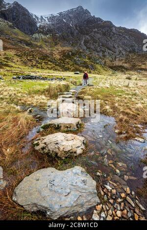 Stepping stones across melt water from the snow covered mountains of Glyder Fawr leading to Llyn Idwal, Snowdonia National Park, North Wales
