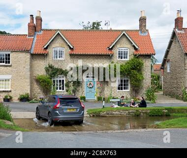 Family having picnic, and car crossing ford, in the village of Hovingham, Ryedale, North Yorkshire, England UK - Stock Photo