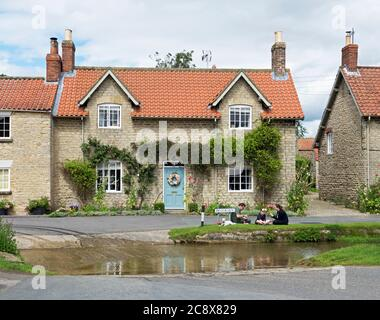 Family having picnic by the ford in the village of Hovingham, Ryedale, North Yorkshire, England UK - Stock Photo