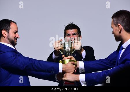 Coworkers or partners fight for winning competition. Business opposition and rivalry concept. Company leaders hold golden prize. Businessmen with mad faces in formal suits on grey background - Stock Photo