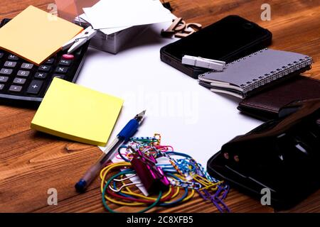 Business and work concept. Office tools on wooden background, close up. Calculator, sticky notes, paper clips, phone, notebook, elastics and hole punch. Stationery on blank business sheet,