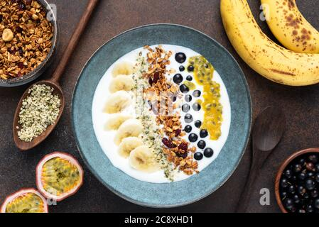 Yogurt bowl with granola and tropical fruits on brown background. Top view. Healthy vegetarian breakfast food