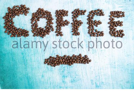 A closeup shot of coffee beans spelling out the word coffee on a rusty blue surface - Stock Photo