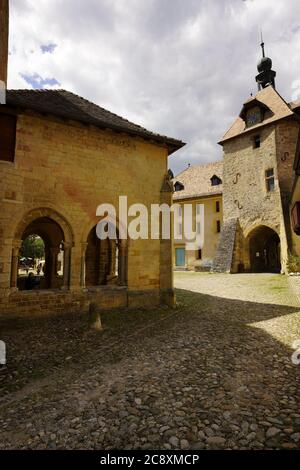 Impressive  Clock Tower of the Romanesque church of Saint-Pierre-et-Saint-Paul in Romainmotier, canton of Vaud, Switzerland. - Stock Photo