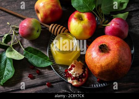 Rosh hashanah (hashana) - jewish new year holiday concept. Traditional symbols: honey, fresh apples and pomegranate on a wooden table. - Stock Photo