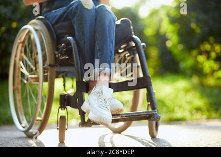 young disabled girl in overall and white trainers sitting with crossed legs on the wheelchair. close up cropped photo.