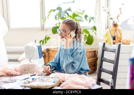 happy long-haired beautiful fashionable designer holding smartphone in hands talking with seamstress about chosen fabric, sitting at office - Stock Photo