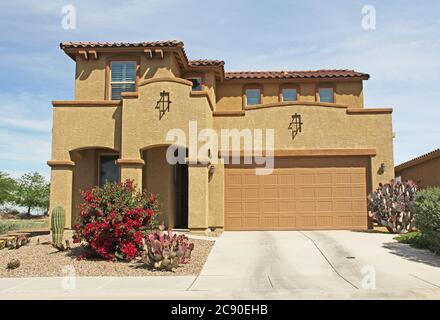 New two-story, brown and tan beige stucco home in Tucson, Arizona, USA with beautiful blue sky and landscaping. - Stock Photo