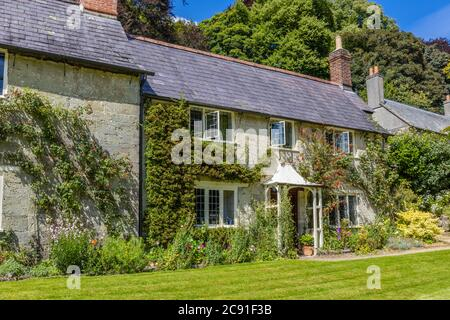 A cottage in a row of traditional stone cottages on Church Lawn in Stourton, a small village near Stourhead, Wiltshire, south-west England - Stock Photo