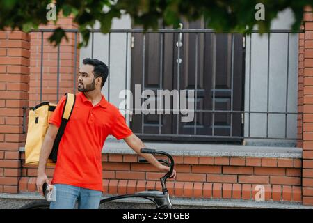 Courier with bicycle, delivery food service at home. Man with mobile phone finds address in city Stock Photo