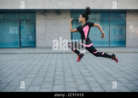 Exercise for weight loss. Woman in sportswear with wireless headphones frozen in air, jumping while running