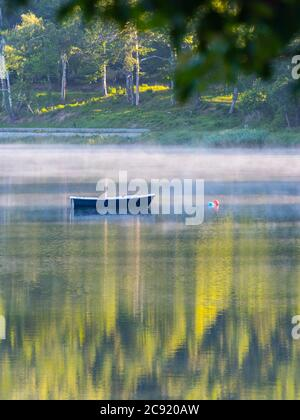 Lonesome boat on lake Bajer in Fuzine Croatia Europe fog mist vapour floating float just about water surface - Stock Photo