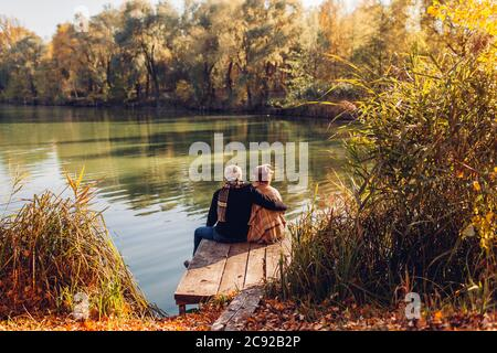 Senior family couple relaxing by autumn lake. Man and woman enjoying nature and hugging sitting on pier - Stock Photo