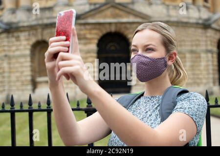 Female Tourist On Vacation Wearing Face Mask During Covid-19 Pandemic Taking Photo On Mobile Phone In Oxford UK Stock Photo
