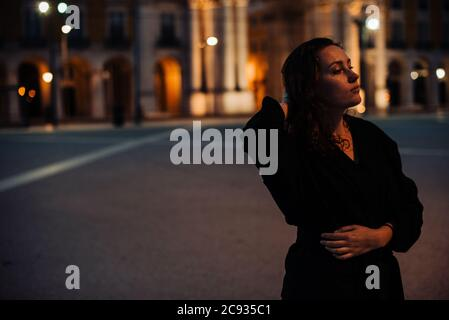 Half length portrait of young woman wearing black, standing alone in the street. Night time, street light, contemplative