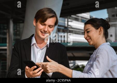 happy young businessman and businesswoman using digital smartphone technology devices and applications in discussing new project business meeting toge - Stock Photo