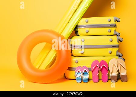 travel bags with family flip flops and pool floats on yellow - Stock Photo