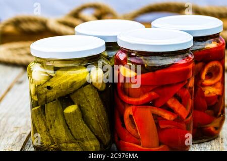 Glass jars with pickled red bell peppers and pickled cucumbers (pickles) isolated. Jars with variety of pickled vegetables. Preserved food concept in