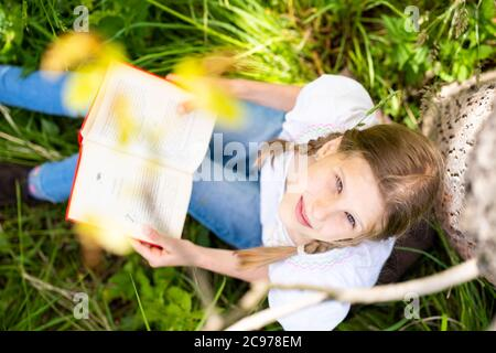 Teenage girl in white T-shirt sitting by the tree in the forest and reading interesting book. Great idea and activity to spend summer holidays. Stock Photo