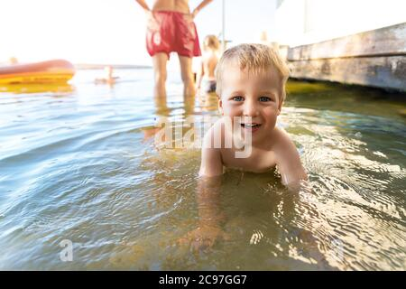 Cute adorable cheerful caucasian little blond toddler boy enjoy having fun playing at lake or river beach water on warm sunset evening time outdoors Stock Photo
