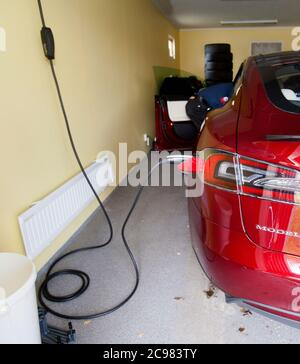 The Tesla electric car. Here while charging in a garage at a home. Photo Jeppe Gustafsson - Stock Photo