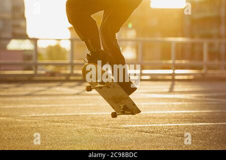 Skateboarder doing a trick at the city's street, close up moments. Young man in sneakers and cap riding and skateboarding on the asphalt. Concept of leisure activity, sport, extreme, hobby and motion. - Stock Photo