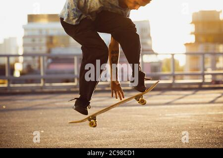 Skateboarder doing a trick at the city's street in summer's sunshine. Young man in sneakers and cap riding and skateboarding on the asphalt. Concept of leisure activity, sport, extreme, hobby and motion. - Stock Photo